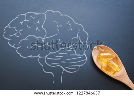 Health care vitamins with Cod liver oil in wooden spoon and brain drawing in chalkboard.