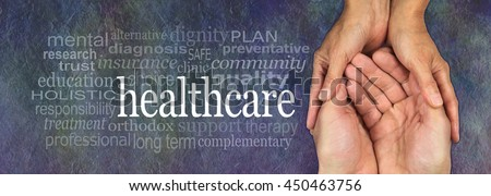 Health Care worker - female hands gently cradling male hands on a rustic dark stone background with a health care word cloud to the left
