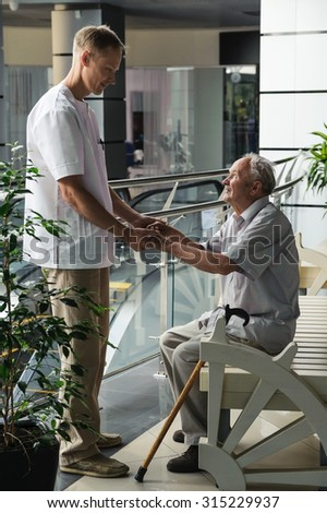 Health-care worker helps the elderly man get up from the bench
