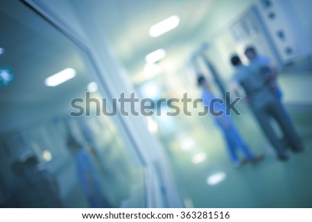 Health care workers are discussing in the hospital corridor, blurred.