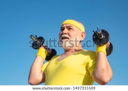 Health club for elderly aged. Senior sport man lifting dumbbells in sport center