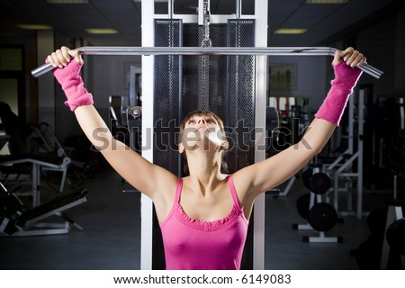 health club: girl in a gym doing weight lifting