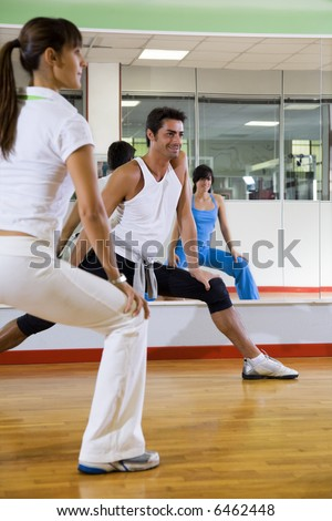 health club: man and women doing stretching and aerobics - stock photo