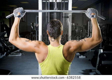 health club: man in a gym doing weight lifting - stock photo