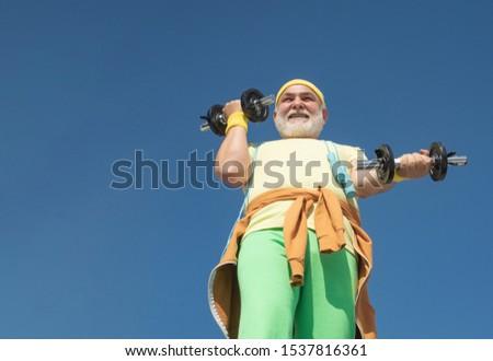 Health club or rehabilitation center for elderly aged pensioner. Freedom retirement concept. Senior sport man lifting dumbbells in sport center