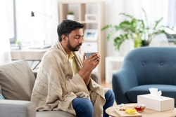 health, cold and people concept - sick young indian man in blanket drinking hot tea with lemon, honey and ginger at home