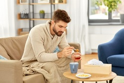 health, cold and people concept - sick young man in blanket drinking hot tea with lemon and honey at home