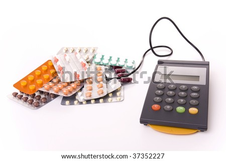 Health cost concept - POS Terminal with a lot of pill tablets (focus on the POS)
