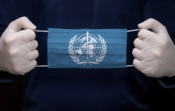 Health employee doctor holding medical face mask with WHO (World Health Organization) flag. Coronavirus (COVID-19) pandemic affects the country.