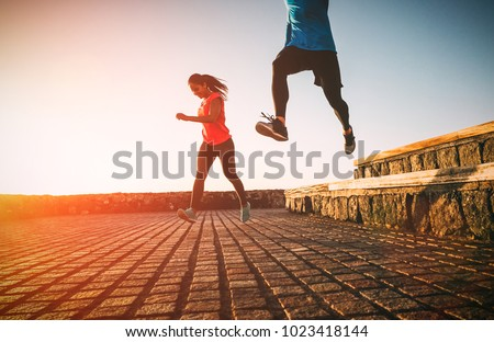 Health fit young couple running together during a magnificent sunset - Athletic friends doing sport outdoor - Sporty people training with jump exercises - Relationship, sport, lifestyle concept  #1023418144