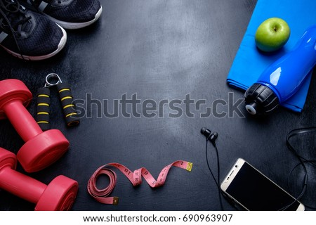 Health fitness background. Sneakers, dumbbell, power grip, green apple. water bottle, blue towel, phone and earphone on dark background.