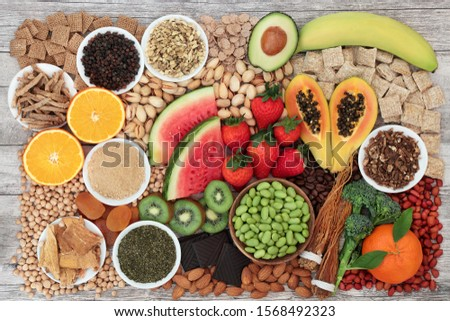 Health food for energy, vitality & fitness with fruit, vegetables, nuts, seeds, legumes, cereal  & herbal medicine.  High in vitamins, minerals antioxidants, smart carbs, protein & omega 3. Flat lay,