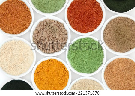 Health food powder superfood selection in white porcelain bowls.
