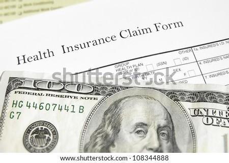 health insurance claim form and cash, closeup