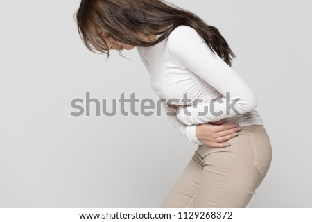Health issues problems concept.Woman suffering from stomach pain, feeling abdominal pain or cramps, side view.Period menstruation, female health problem, aching belly and gynecology