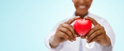 health, medicine and charity concept - close up of african american female doctor hands holding red heart over blue background