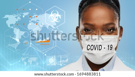 health, medicine and coronavirus epidemy concept - african american female doctor wearing face protective medical mask over world map with charts and biohazard symbol on blue background