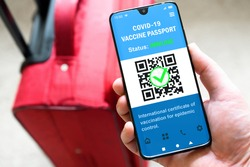 Health passport of COVID-19 vaccination in mobile phone for travel, tourist holds smartphone with passport app. Digital certificate, proof of coronavirus immunization. Corona vaccine pass and tourism.