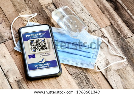 health passport on wooden table with the french text 'passeport sanitaire' means 'digital green pass' and  'vaccination certifiée' means 'certified vaccination' Stock photo ©