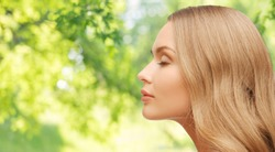 health, people and beauty concept - beautiful young woman face over green natural background