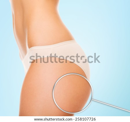 health people bodycare and beauty concept close up of woman buttocks and magnifier over blue background
