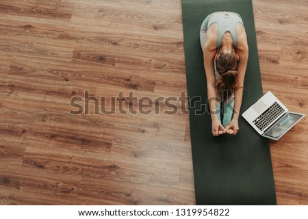 Health practice concept. Top view portrait of young flexible female doing seated forward bend yoga exercise on mat with laptop. Copy space on left