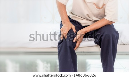 Health problem concept; old woman suffering from knee pain at home.
