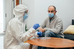 Health professional in a PPE suit, mask, face shield taking a nasal culture sample in the coronavirus pandemic during a home visit. Antigen test of an elderly patient.
