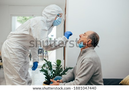 Health Professional in PPE suit and face shield introducing a nasal swab to a senior adult patient at his house. Rapid Antigen Test kit to analyze nasal culture sampling while coronavirus Pandemic.