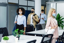 Health protection and return to work after quarantine covid-19. Multiracial young employees in protective masks and with bags go to workplaces in morning in modern office with green plants, copy space