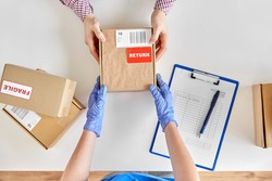 health protection, delivery and mail service concept - customer making return of parcel or purchase and worker in protective gloves receiving box