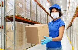 health protection, safety and pandemic concept - delivery woman in face protective medical mask and gloves holding parcel box over warehouse background