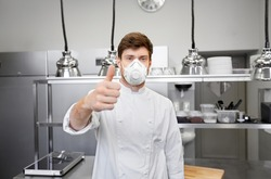 health protection, safety and pandemic concept - male chef cook wearing face protective mask or respirator over restaurant kitchen background