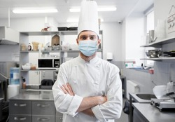 health protection, safety and pandemic concept - male chef cook wearing face protective medical mask over restaurant kitchen background