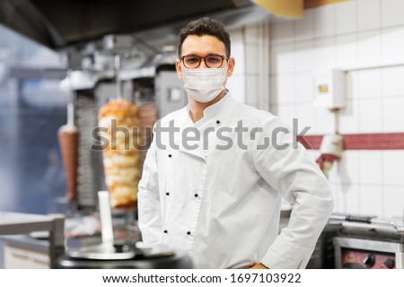 health protection, safety and pandemic concept - male chef cook wearing face protective medical mask over kebab shop kitchen background