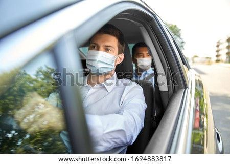 health protection, safety and pandemic concept - male taxi driver wearing face protective medical mask driving car with passenger Stockfoto ©