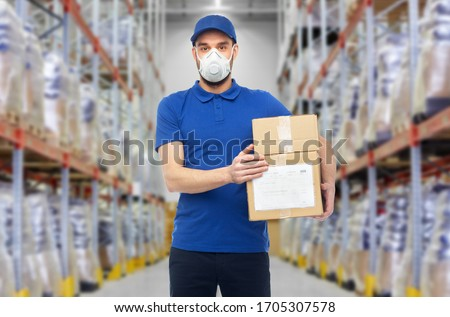 health, safety and pandemic concept - happy delivery man in blue uniform wearing face protective mask or respirator for protection from virus with clipboard over warehouse background