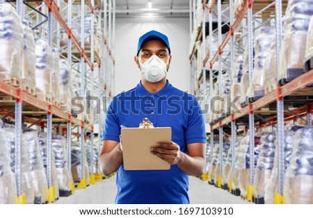 health, safety and pandemic concept - happy indian delivery man in blue uniform wearing face protective mask or respirator for protection from virus with clipboard over warehouse background