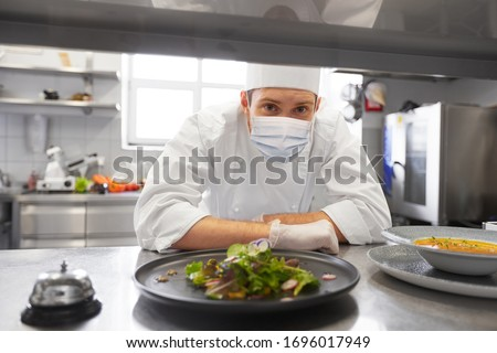health, safety and pandemic concept - male chef cook wearing face protective medical mask for protection from virus disease with plate of soup and salad at restaurant kitchen