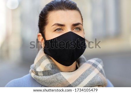 health, safety and pandemic concept - young woman wearing black face protective reusable barrier mask outdoors Photo stock ©