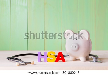 Health Savings Account HSA concept with white  piggy bank, stethoscope wood block letters and green background