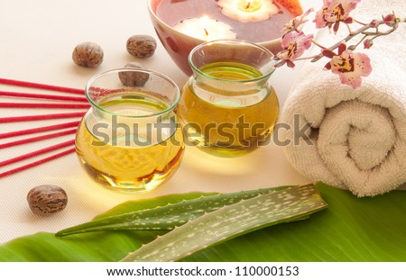 Health spa, two bottles of essential oil with of fresh aloe vera, towels, candle, incense, one with orchid flowers.