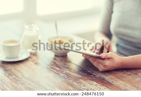 health, technology, internet, food and home concept - close up of woman reading morning news from tablet pc computer