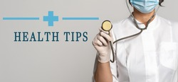 Health Tips - concept of text on gray background. Nearby is a cropped view of doctor in white coat, protective face mask and stethoscope. Medical concept
