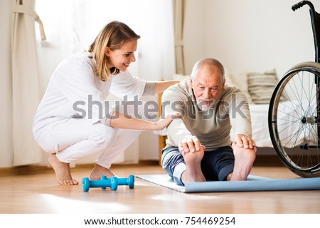 Health visitor and a senior man during home visit. A nurse or a physiotherapist helping a senior man exercise.