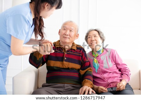 Health visitor and  senior couple during home visit