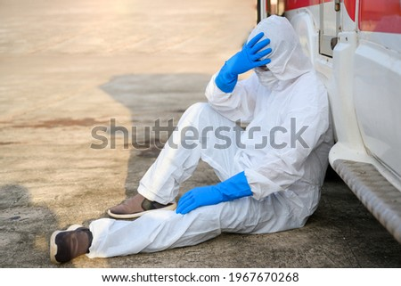 Health worker Standing at an emergency ambulance Wear a PPE uniform Ambulances carry the bodies of the coronavirus, COVID-19 doctors wearing ppe clothes Sitting sad and tired