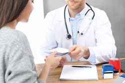 Healthcare. A patient in a doctor's office. The doctor enters recommendations and prescriptions.