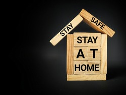 Healthcare and Awareness Concept - Stay safe stay at home text on wooden blocks background. Stock photo.