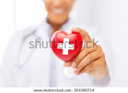 healthcare and medicine concept - female african american doctor holding heart with red cross symbol #301080554